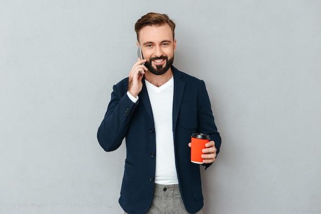 スマートフォンで話しているビジネス服で笑顔のひげを生やした男 無料写真