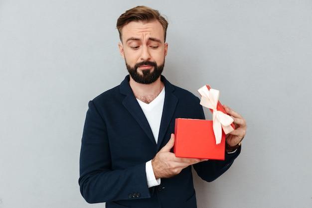 ギフトを開くビジネス服で驚いてひげを生やした男のイメージ 無料写真