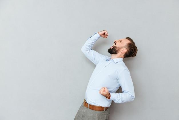 Вид сбоку кричащего счастливого бородатого мужчины в деловой одежде Бесплатные Фотографии