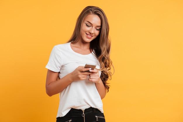 携帯電話でチャット陽気なかわいい美しい若い女性 無料写真