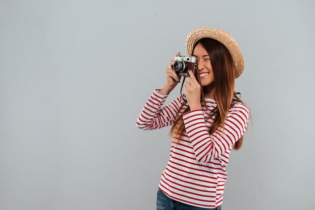 セーターと帽子の写真を作るアジアの女性の笑顔 無料写真