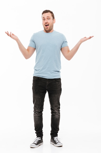 Полнометражный портрет счастливого человека с щетиной в случайных вырванных руках, выражающих удивление или волнение Бесплатные Фотографии