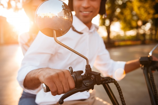 公園でモダンなバイクに乗って幸せなアフリカのカップルのトリミングされた画像 無料写真