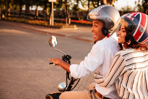 公園でモダンなバイクに乗ってうれしそうなアフリカカップルの側面図 無料写真
