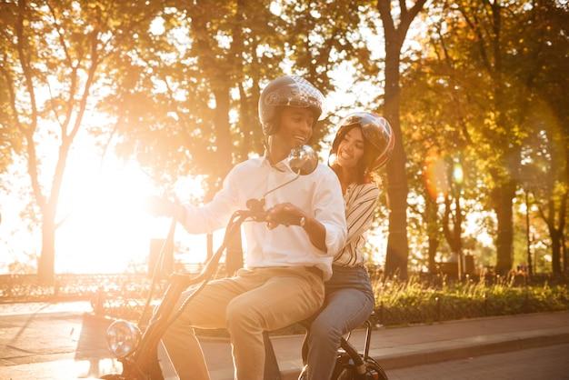 のんきなアフリカのカップルが公園で現代のバイクに乗って、お互いに見ている 無料写真