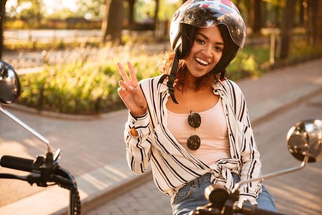 現代のバイクを屋外に座って見ているとカメラで平和を見せながらモトヘルメットで幸せなアフリカの女 無料写真