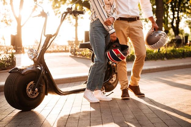公園で現代のバイクに近いポーズをとって若いアフリカカップルのトリミングされた画像 無料写真