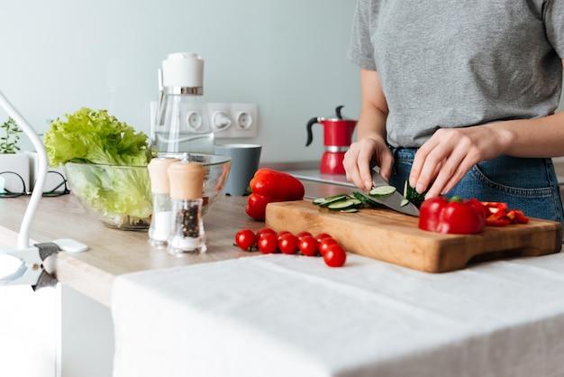 野菜をスライスする女性の手の肖像画を間近します。 無料写真
