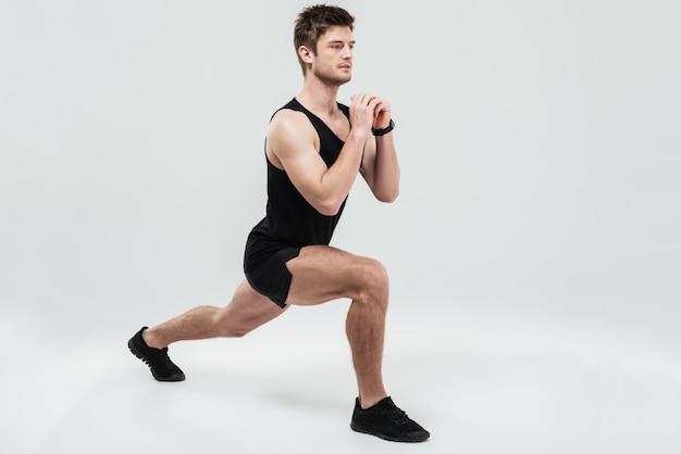 スクワット運動をしている若い集中男の肖像 無料写真