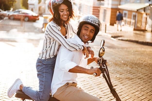 路上で現代のバイクに乗って満足しているアフリカのカップルの側面図 無料写真