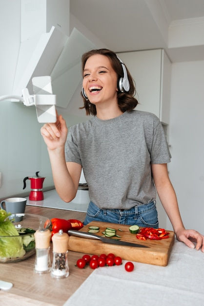 ヘッドフォンで笑う若い女性の肖像画 無料写真
