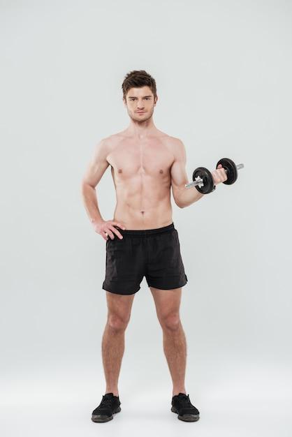 立っているとダンベルを保持しているハンサムなフィットスポーツマンの肖像画 無料写真