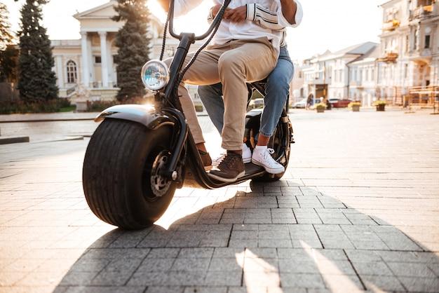 路上で現代のバイクに乗るアフリカのカップルのトリミングされた画像 無料写真