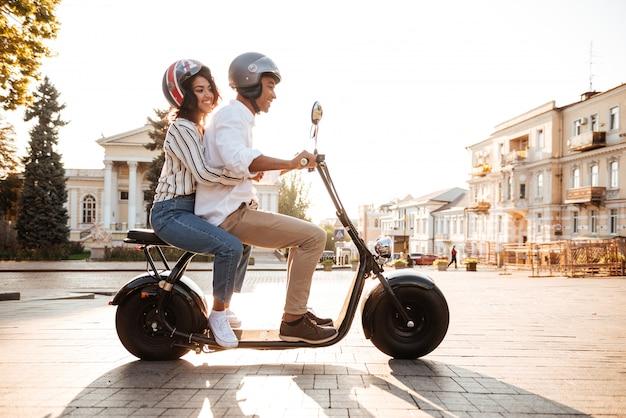 路上で現代のバイクに乗る若いアフリカカップルの完全な長さの側面図 無料写真