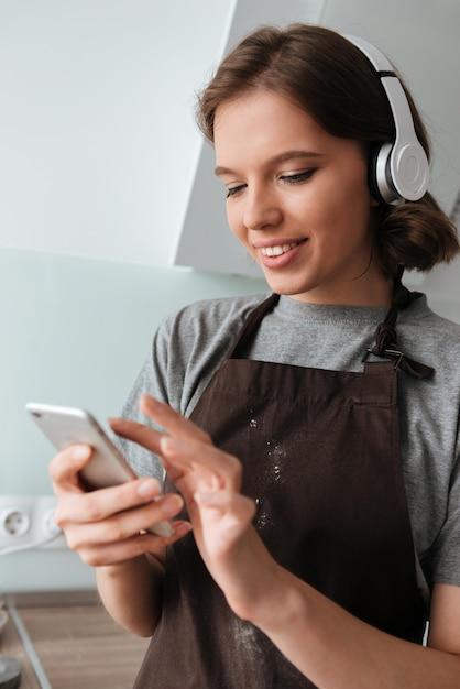 エプロンを着ているヘッドフォンで笑顔の若い女性の肖像画 無料写真