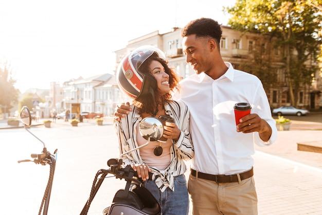 路上のモダンなバイクの近くに立って、お互いに見ながらコーヒーを飲みながら幸せな若いアフリカカップル 無料写真
