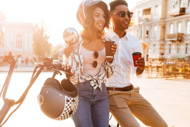 路上で現代のバイクの近くに立って、よそ見しながらコーヒーを飲みながら幸せな若いアフリカカップル 無料写真