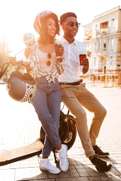 通りのモダンなバイクの近くに立って、よそ見しながらコーヒーを飲みながら幸せな若いアフリカカップルの完全な長さの画像 無料写真
