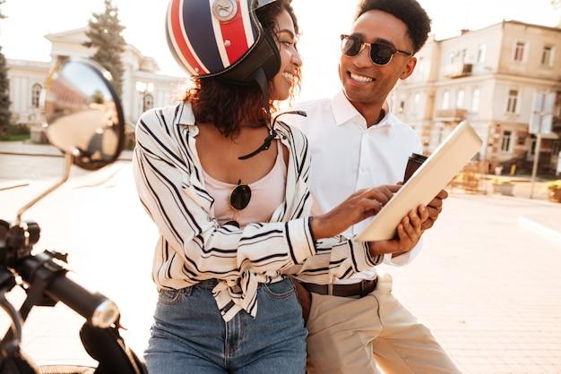 現代のバイクの上に座って、お互いを見ながら路上でタブレットコンピューターを使用してアフリカのカップルの笑顔 無料写真