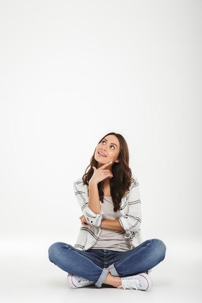 ロータスで座っているカジュアルな服装でブルネットの女性の全身画像は、白い壁に分離された上向きの顔と率直な笑顔で床にポーズします。 無料写真