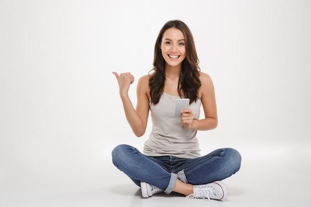 銀のスマートフォンを使用して床に足を組んで座っている長い茶色の髪と満足している女性の写真 無料写真