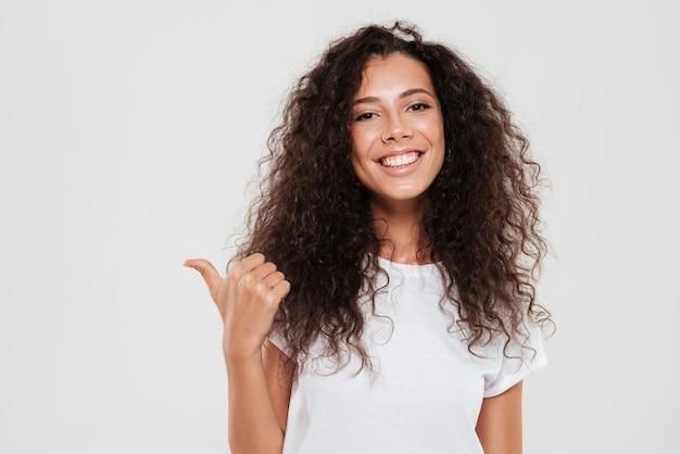 親指を現して笑顔の巻き毛の女性 無料写真