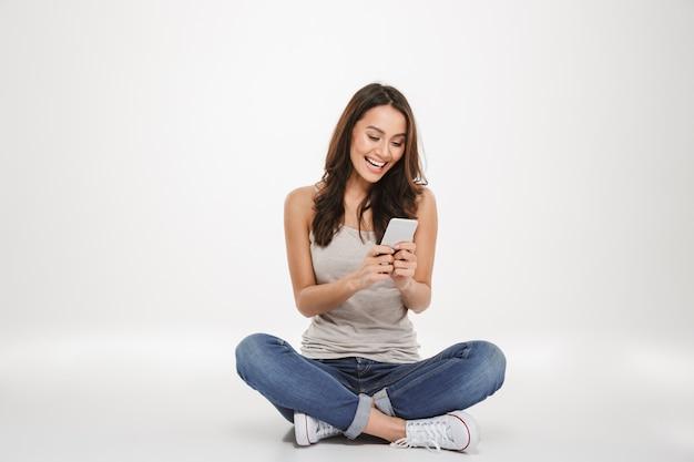床に座って、灰色のスマートフォンでメッセージを書いて幸せなブルネットの女性 無料写真