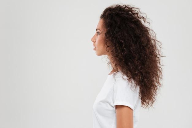 かなり巻き毛の女性がプロファイルでポーズ 無料写真
