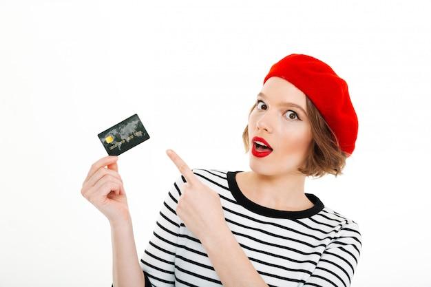 カメラを探していると分離されたクレジットカードを指して深刻な驚く女性 無料写真