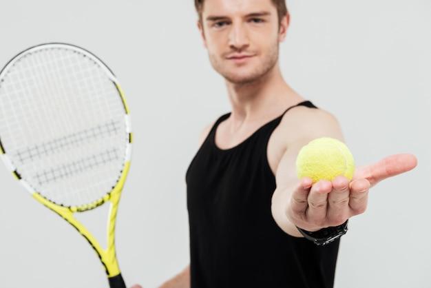 Красивый молодой спортсмен, держа теннисный мяч и ракетку Бесплатные Фотографии