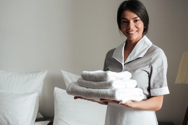 新鮮なきれいな折り畳まれたタオルを保持しているホテルのメイドの肖像画 無料写真