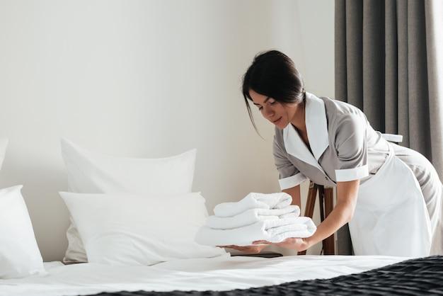 新鮮な白いバスタオルのスタックを置く若いホテルのメイド 無料写真