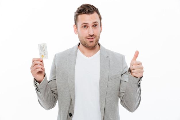クレジットカードを保持している親指を示すハンサムな青年実業家。 無料写真