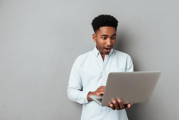 Возбужденный афро-американский мужчина, глядя на экран ноутбука Бесплатные Фотографии