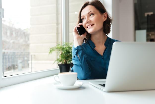 携帯電話で話している幸せな笑顔の女性 無料写真