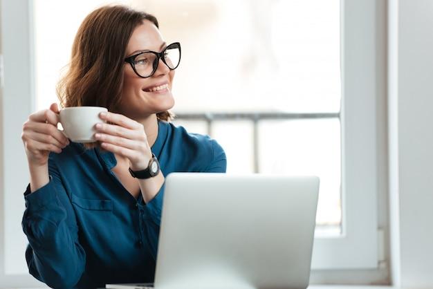 Счастливая усмехаясь женщина держа чашку кофе Бесплатные Фотографии