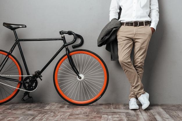 自転車の近くに立っている服を着た半分の男性の体 無料写真