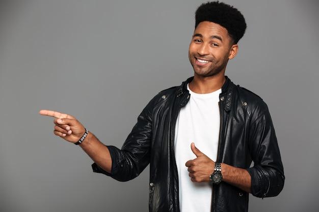 Счастливый молодой афро-американский мужчина в кожаной куртке, указывая с фигурой, показывая пальцем вверх жест, глядя Бесплатные Фотографии
