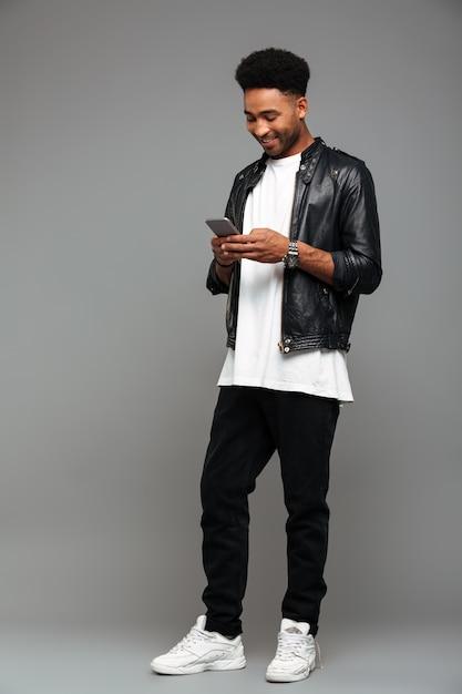 スマートフォンでメッセージを入力して幸せな魅力的なアフロアメリカン男 無料写真