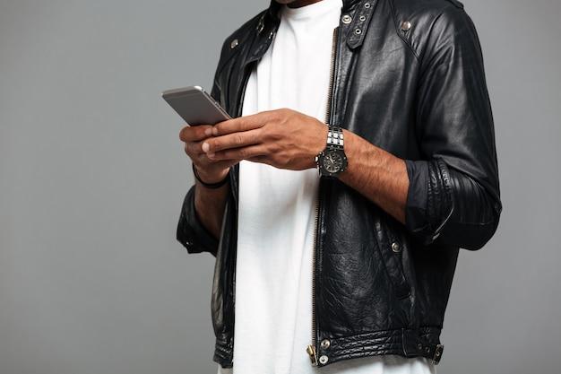 スマートフォンで革のジャケットでアフロアメリカンの男 無料写真