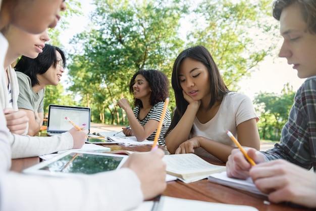 座っていると勉強している若い学生の多民族グループ 無料写真