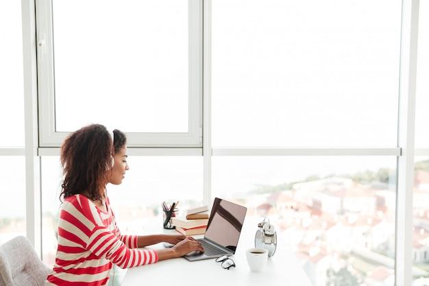 Молодая уверенно африканская женщина в наушниках работает на ноутбуке Бесплатные Фотографии