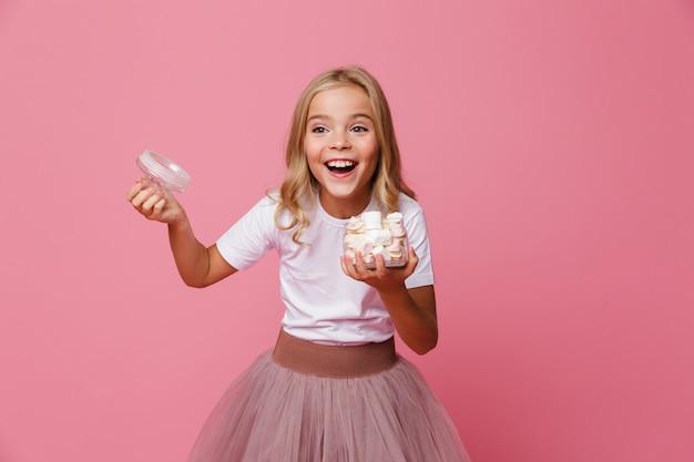 マシュマロの開いている瓶を保持している幸せな少女の肖像画 無料写真