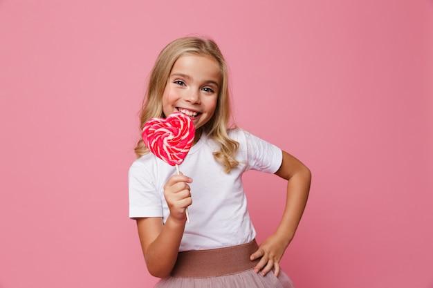 Портрет счастливой маленькой девочки, держащей леденец в форме сердца Бесплатные Фотографии