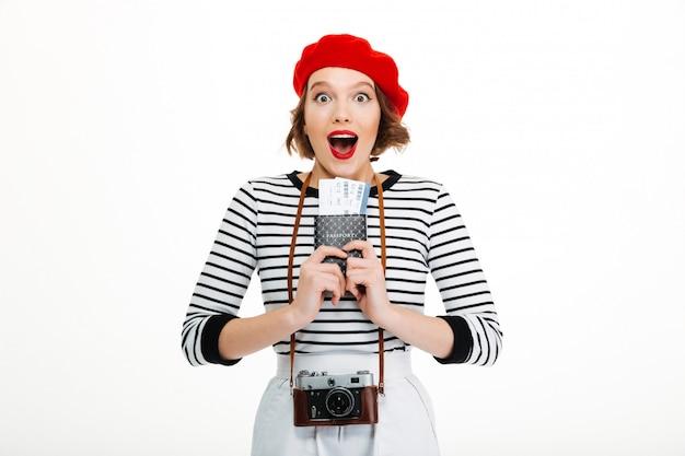 チケットでパスポートを保持しているカメラで驚いた観光客の女性。 無料写真