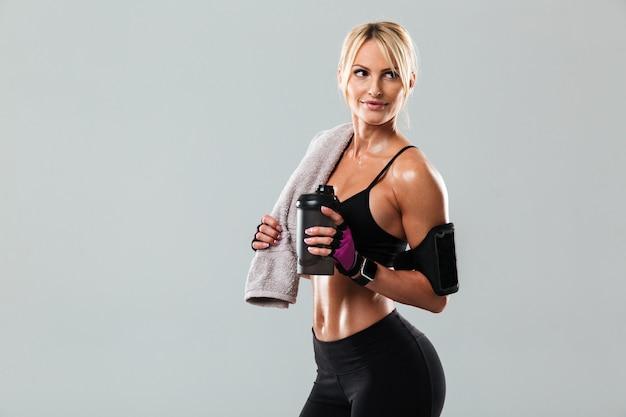 Улыбающаяся блондинка спортсменка держит полотенце Бесплатные Фотографии