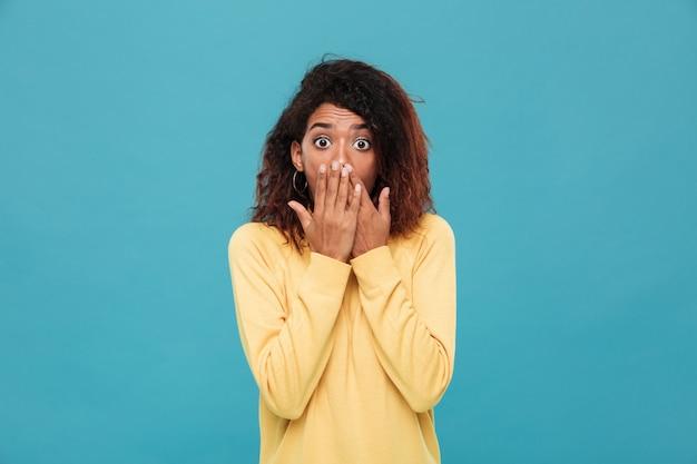Потрясенная африканская женщина в свитере покрывая ее рот Бесплатные Фотографии