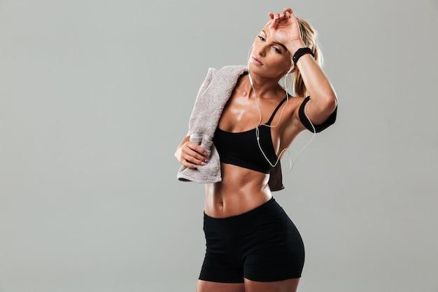 音楽を聴いて立っている疲れている若いスポーツ女性 無料写真