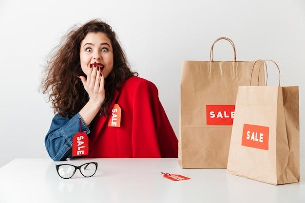 Возбужденная шопоголика радостная девушка сидит с бумажными сумками Бесплатные Фотографии