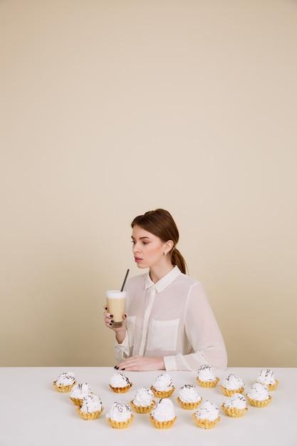 集中している若い女性がコーヒーを保持しているカップケーキに近いポーズ 無料写真